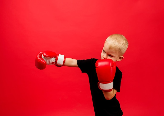 A little boy boxer in red boxing gloves stands making a punch on red