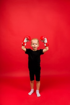 A little boy boxer stands and holds up his hands boxing gloves on red