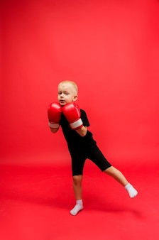 A little boy boxer stands tall in red boxing gloves on red