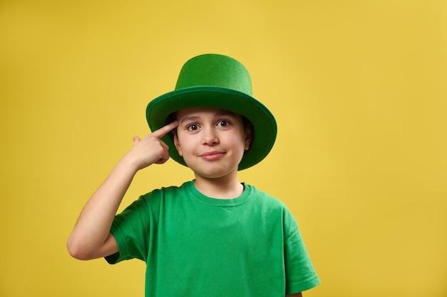 小さな男の子は、黄色い表面に立っている彼の寺院に人差し指を持ってきます