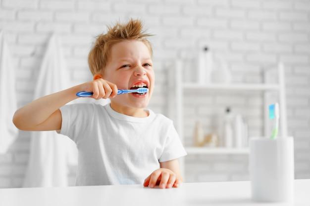 小さな男の子がバスルームで熱心に歯を磨く