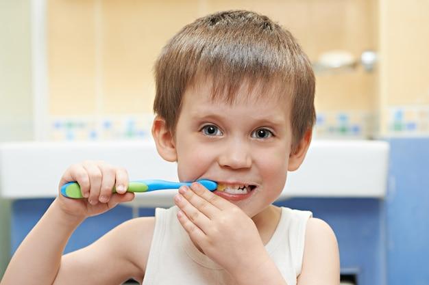 小さな男の子がバスルームで歯を磨く