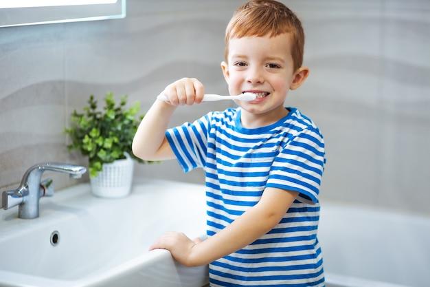 Little boy brushing teeth in bathroom