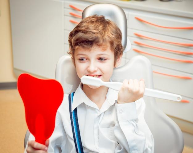 大きなブラシで歯を磨く少年