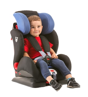 Little boy buckled in car seat on white