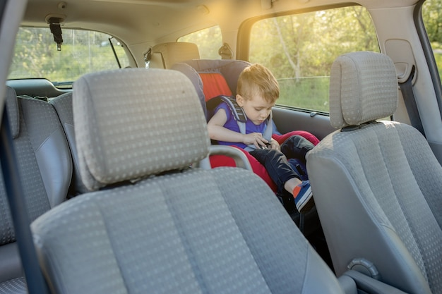 Little boy buckled up with seatbelt inside the car. vehicle and transportation concept