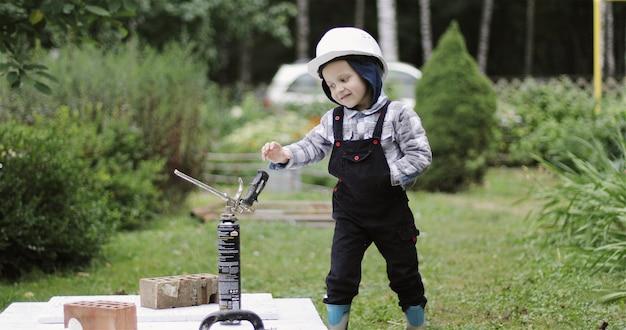 白いヘルメットの小さな男の子ビルダーは、ポリウレタンフォームのシリンダーで遊ぶ