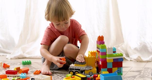 Little boy builds colored blocks