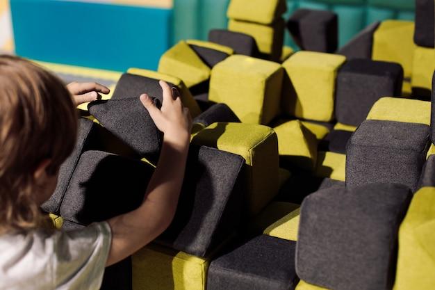 Маленький мальчик строит из мягких кубиков в детском научно-образовательном центре. проблемы со связью. организация игровых зон. центры развития детей.