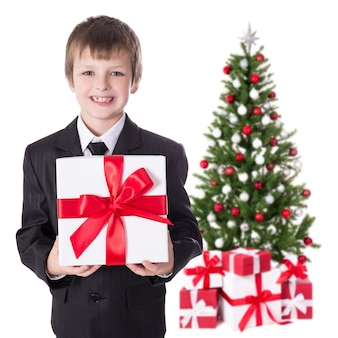 Little boy in business suit with gift box and christmas tree isolated on white background