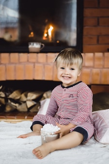 Little boy by the fire and having hot chocolate with marshmallows