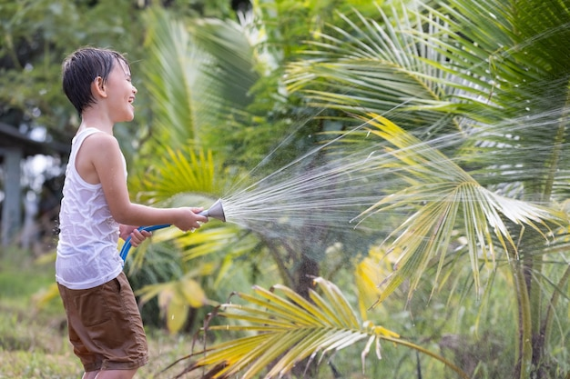 어린 소년은 석양에 물을 주는 고무 호스에서 녹색 채소에 물을 주는 식물을 돌봅니다