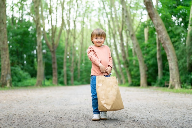 Little boy carrying a paper bag after a successful shopping i a moll. shopping with children during sales. black friday concept.