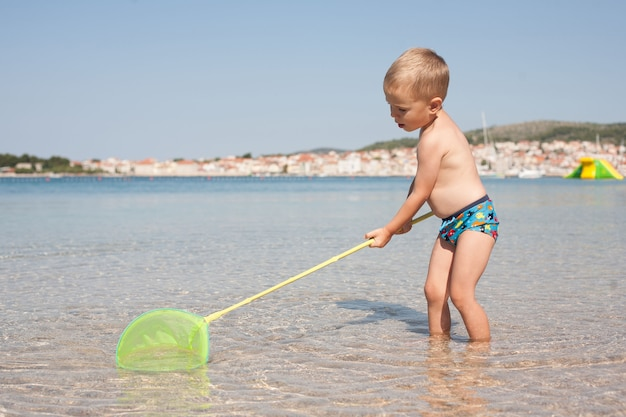 Little boy catches fish with a small bright net in the sea