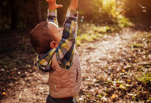 Little boy catching bubbles in autumn forest
