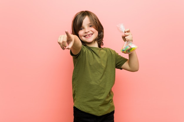 Little boy caucasian holding candies cheerful smiles pointing to front.