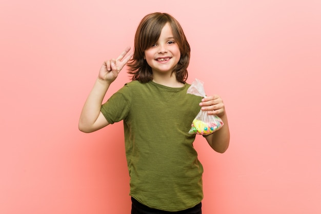 Little boy caucasian holding candies showing victory sign and smiling broadly.