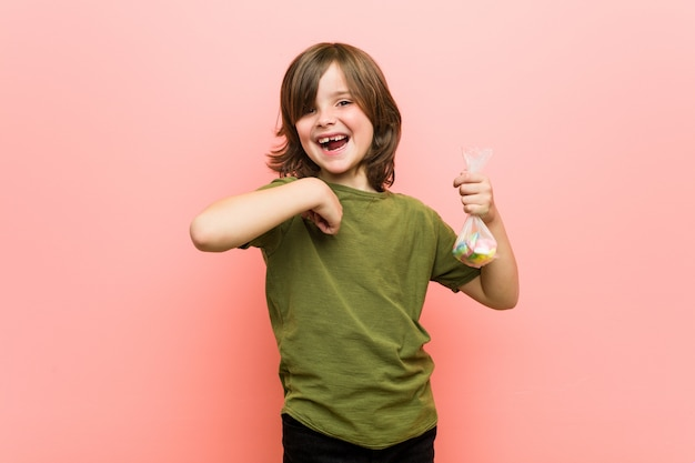Little boy caucasian holding candies surprised pointing at himself, smiling broadly.