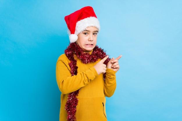 サンタの帽子を身に着けているクリスマスの日を祝う少年は、コピースペースに人差し指で指しているショックを受けた。