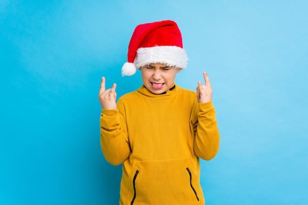 指でロックジェスチャーを示す分離されたサンタ帽子をかぶっているクリスマスの日を祝う少年