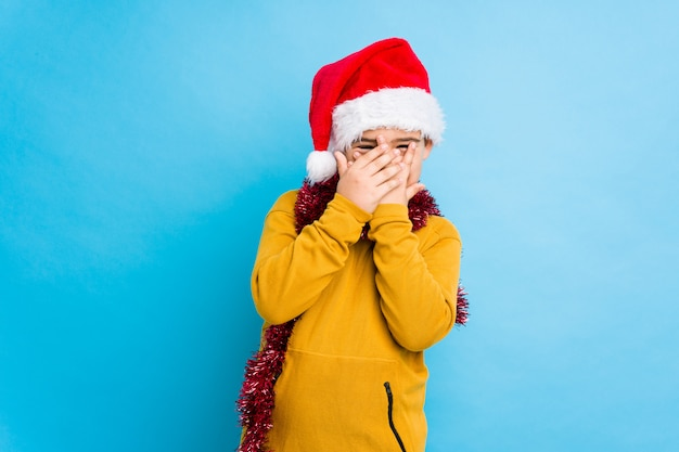 Little boy celebrating christmas day wearing a santa hat isolated blink through fingers frightened and nervous.