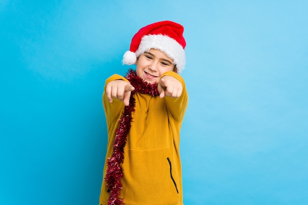 Little boy celebrating christmas day wearing a santa hat isolated cheerful smiles pointing to front.