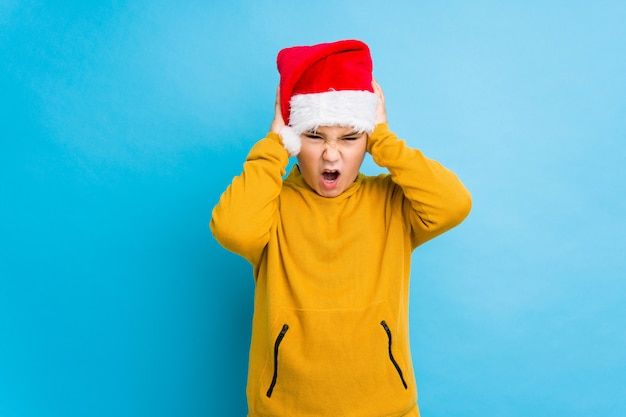 Little boy celebrating christmas day wearing a santa hat isolated covering ears with hands trying not to hear too loud sound.