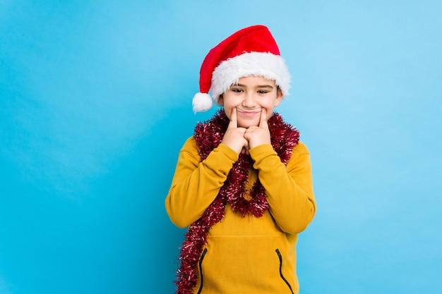 Little boy celebrating christmas day wearing a santa hat isolated doubting between two options.