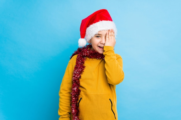 Little boy celebrating christmas day wearing a santa hat isolated having fun covering half of face with palm.