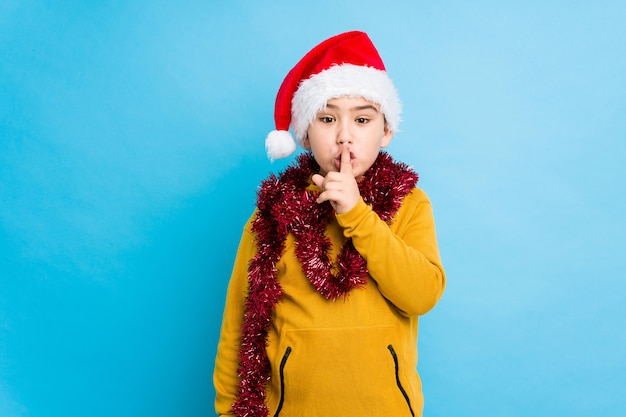 Little boy celebrating christmas day wearing a santa hat isolated keeping a secret or asking for silence.