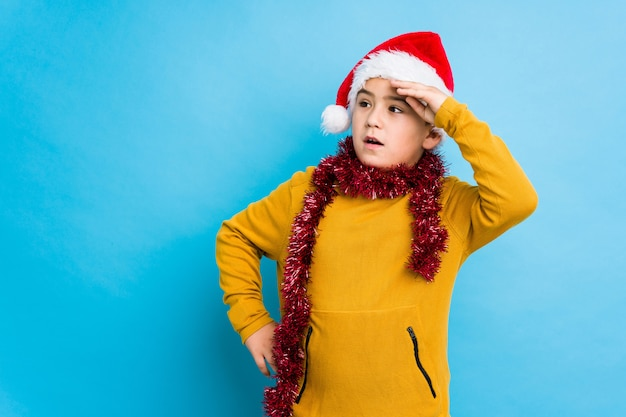 Little boy celebrating christmas day wearing a santa hat isolated looking far away keeping hand on forehead.