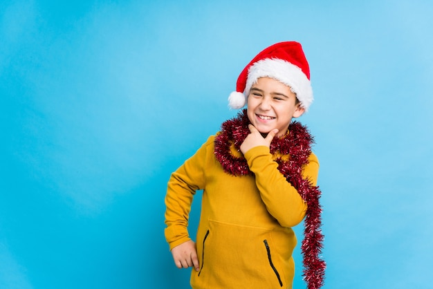 Little boy celebrating christmas day wearing a santa hat isolated looking sideways with doubtful and skeptical expression.