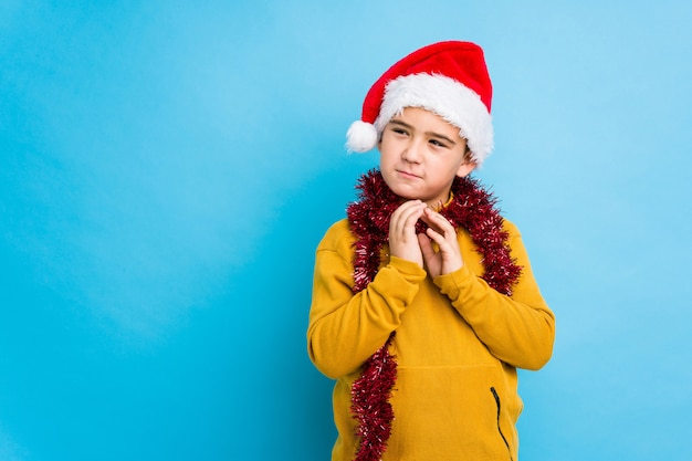 Little boy celebrating christmas day wearing a santa hat isolated making up plan in mind, setting up an idea.