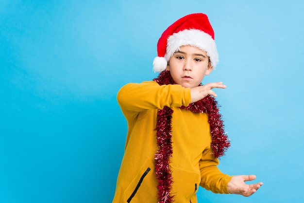 Little boy celebrating christmas day wearing a santa hat isolated shocked and amazed holding a copy space between hands.