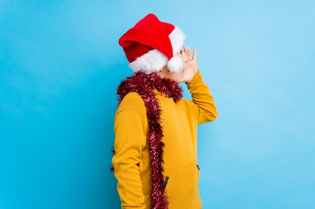 Little boy celebrating christmas day wearing a santa hat isolated shouting and holding palm near opened mouth.