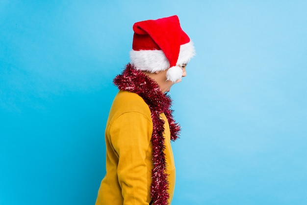Little boy celebrating christmas day wearing a santa hat isolated shouting towards a copy space