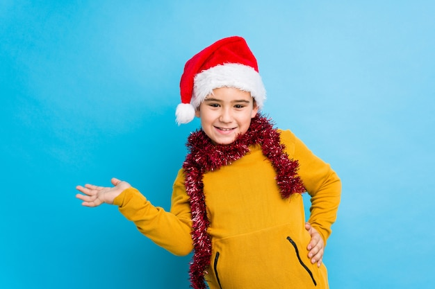 Little boy celebrating christmas day wearing a santa hat isolated showing a copy space on a palm and holding another hand on waist.