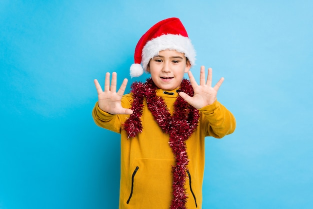 Little boy celebrating christmas day wearing a santa hat isolated showing number ten with hands.