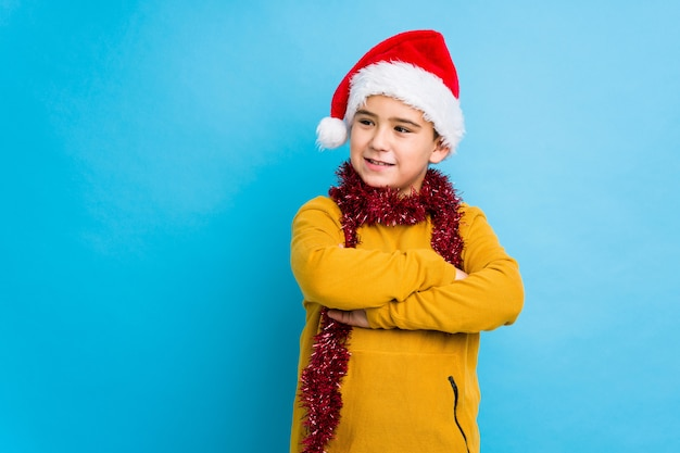 Little boy celebrating christmas day wearing a santa hat isolated smiling confident with crossed arms.