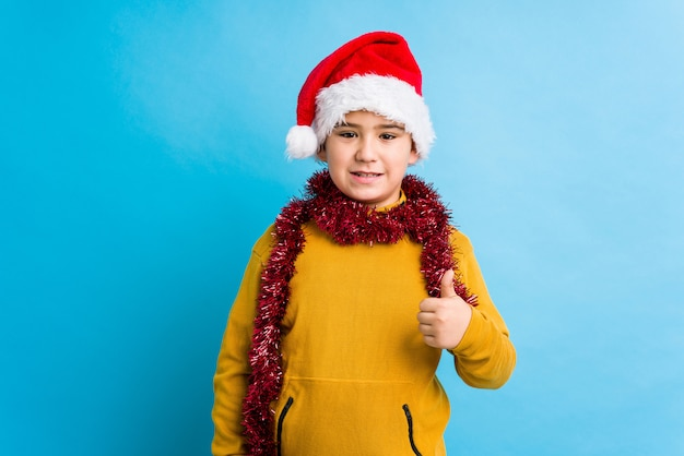 Little boy celebrating christmas day wearing a santa hat isolated smiling and raising thumb up