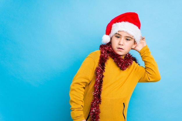 Little boy celebrating christmas day wearing a santa hat isolated trying to listening a gossip.