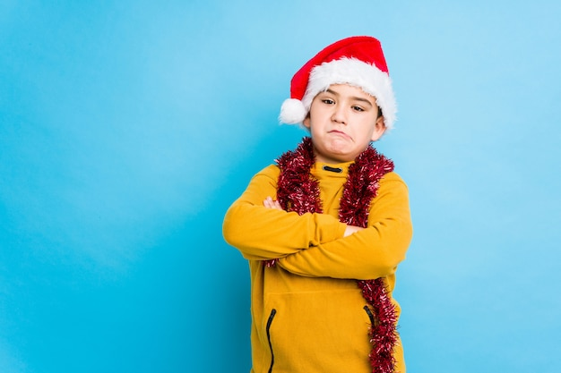 Little boy celebrating christmas day wearing a santa hat isolated unhappy looking in camera with sarcastic expression.