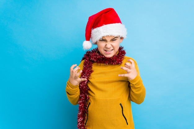 Little boy celebrating christmas day wearing a santa hat isolated upset screaming with tense hands.