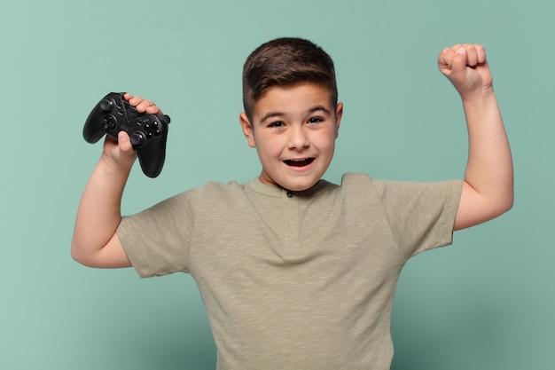 ゲームのジョイスティックで勝利を祝う小さな男の子