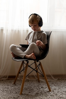 Little boy on chair at home using tablet and headphones