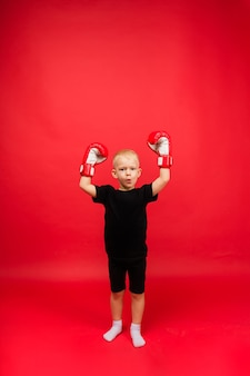 Little boy champion boxer in red boxing gloves held his hands up against a red wall