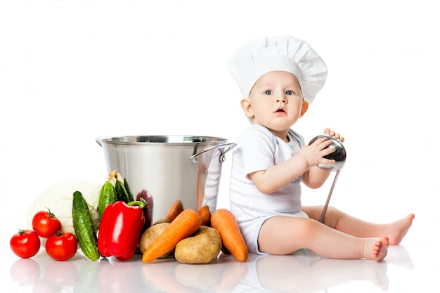 Little boy in chef's hat with ladle, pan and vegetables