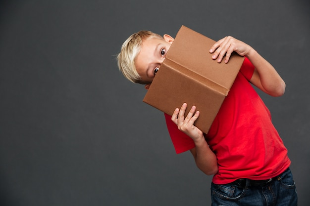Little boy child covering face with book.
