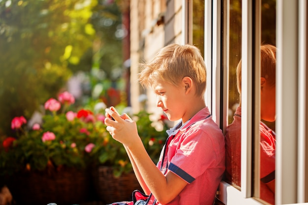 Little boy child kid playing games on smartphone mobile phone ou