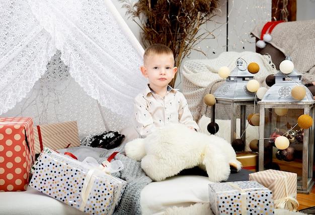 작은 소년 아이 아이 장식 된 집에서 크리스마스 선물 상자 사이에 앉아. 메리 크리스마스와 해피 홀리데이!